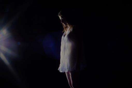 暗闇で沈み込む女性